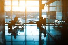 Kontur av ett oigenkännligt affärsresandefolk på den internationella flygplatsen Royaltyfria Bilder