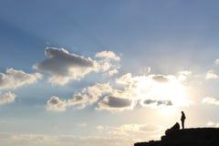 Kontur av ett par som framme står av solnedgången arkivbild