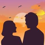 Kontur av ett par som kysser mot en solnedgånghimmel Royaltyfri Fotografi