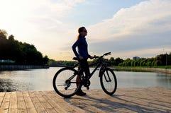 Kontur av ett sportigt ung flickaanseende med en cykel royaltyfri bild