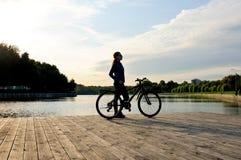 Kontur av ett sportigt ung flickaanseende med en cykel arkivfoton