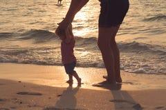 Kontur av fadern och den lilla dottern som lär att gå på solnedgångstranden Kvinnligt spädbarn tio gamla månader lycklig familj arkivfoto