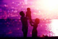Kontur av familjen i utomhus- sjösidasolnedgång Royaltyfria Foton
