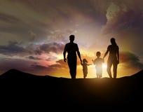 Kontur av familjen som vänder mot solnedgången Arkivfoto