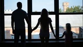 Kontur av familjinnehavhänder vid fönstret stock video