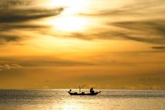 Kontur av fiskare i fartyget på havet med den gula och orange solen i bakgrunden Arkivfoto