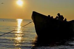 Kontur av fiskare som arbetar i solnedgången Arkivbild