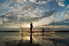 Kontur av fiskare som kastar netto fiske i solnedgångtid på W Royaltyfria Bilder