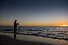 Kontur av fiskaren med hatten på stranden med fiskstånganseende på fiske för havsvatten på solnedgången med härlig orange himmel  Royaltyfria Bilder