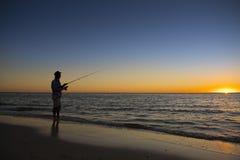 Kontur av fiskaren med hatten på stranden med fiskstånganseende på fiske för havsvatten på solnedgången med härlig orange himmel  Arkivfoton