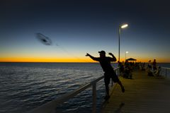 Kontur av fiskaren med hatten som kastar fisken som står netto på havsskeppsdockafiske på solnedgången med härlig orange himmel i Arkivfoton
