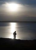 Kontur av fiskaren med metspöet på kusten av dammet Royaltyfri Foto