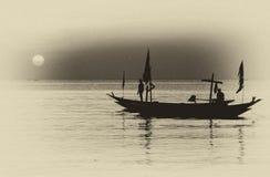 Kontur av fiskaren och fartyg som svävar på strandremsan Royaltyfri Fotografi