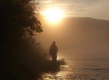 Kontur av fiskaren på floden i soluppgång Royaltyfri Bild