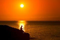 Kontur av fiskaresammanträde med stången på solnedgången Arkivfoto