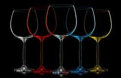 Kontur av flerfärgat vinexponeringsglas på svart Arkivbilder