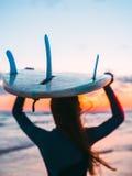 Kontur av flickan med surfingbrädan på stranden på solnedgången eller soluppgång Surfare och hav med vågor Royaltyfria Foton