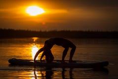 Kontur av flickan som övar yoga på SUP i solnedgången på sjön Velke Darko arkivbild