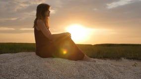 Kontur av flickan som tycker om solnedgången som sitter på sand, diagram av den härliga kvinnan i harmoni med naturen, begreppsso arkivfilmer