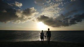 Kontur av flickor på stranden på solnedgången arkivfilmer