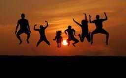 Kontur av folk som hoppar på solnedgången Royaltyfri Bild