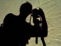 Kontur av fotografen på stranden Arkivbild