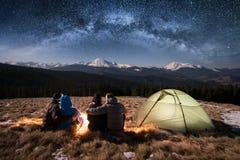 Kontur av fyra personer som tillsammans mycket sitter bredvid läger och tältet under härlig natthimmel av stjärnor och den mjölka Arkivbild