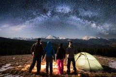 Kontur av fyra personer som tillsammans mycket står bredvid läger och tältet under härlig natthimmel av stjärnor och den mjölkakt Arkivbild