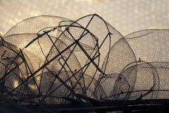 Kontur av gamla fisknät mot soluppgånghimmel Royaltyfria Foton