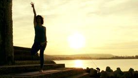 Kontur av gymnastik för kvinnautbildningsyoga på solnedgången arkivfilmer