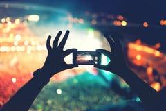 Kontur av händer genom att använda kameratelefonen för att ta bilder och video på popkonserten, festival Fotografering för Bildbyråer
