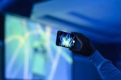 Kontur av händer med en smartphone på en konsert fotografering för bildbyråer