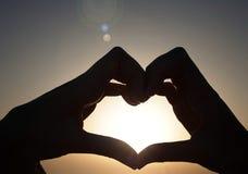 Kontur av händer som är förälskade på solnedgånghimlen royaltyfri bild