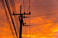 Kontur av höga spänningskraftledningar mot orange färgrikt s Arkivbild