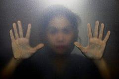 Kontur av handen bak glass förgrund Arkivbild
