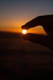 Kontur av handen som griper solen Royaltyfri Fotografi