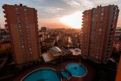 Kontur av hyreshusar mot färgrik himmel på solnedgången Royaltyfria Bilder