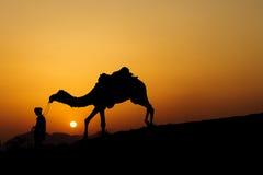 Kontur av kamelaffärsmannen som korsar sanddyn Arkivbild