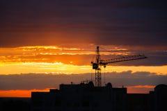 Kontur av konstruktionskranen och byggnad på solnedgånghimmelbakgrund royaltyfri fotografi