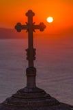 Kontur av korset mot solen under solnedgång Arkivfoton