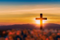 Kontur av korset på bergsolnedgångbakgrund arkivfoton