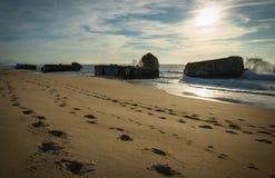Kontur av krigblockhuset på scenisk härlig seascape för sandig strand med vågor på Atlantic Ocean royaltyfri bild