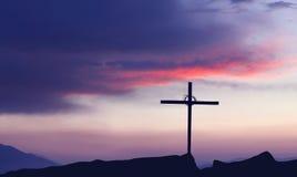 Kontur av kristenkorset på soluppgång- eller solnedgångbegreppet av beträffande arkivbilder