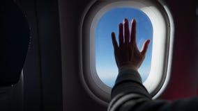 Kontur av kvinnahanden över fönstret av flygplanet Moln och himmel som sett till och med fönstret av ett flygplan, luftnivå arkivfilmer