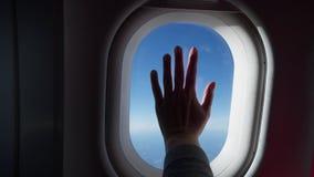 Kontur av kvinnahanden över fönstret av flygplanet Moln och himmel som sett till och med fönstret av ett flygplan, luftnivå lager videofilmer