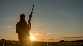 Kontur av kvinnajägaren Det står i ett pittoreskt ställe med ett vapen på solnedgången Sportar som skjuter och jagar begrepp Arkivbilder
