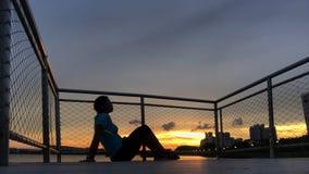 Kontur av kvinnan mot solnedgång på en pir Arkivfoto