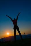 Kontur av kvinnan på solnedgången Arkivbild
