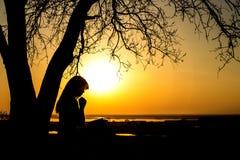 Kontur av kvinnan som ber till guden i naturwitthen bibeln på solnedgången, begreppet av religionen och andlighet arkivbild