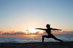 Kontur av kvinnan som gör yoga på stranden på soluppgång royaltyfri fotografi